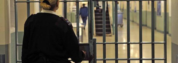 A prison officer locks a door
