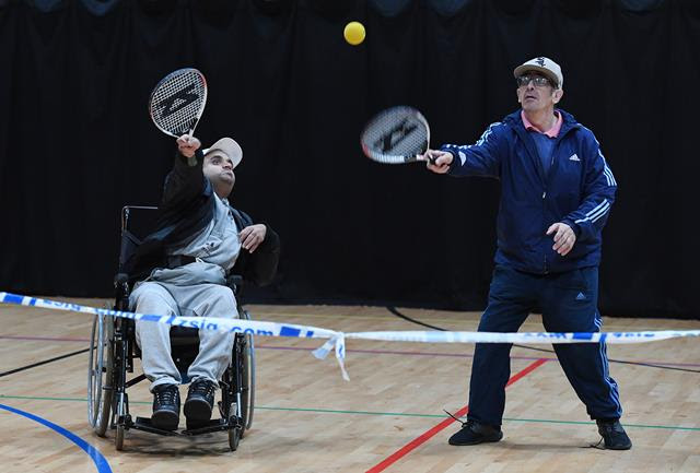 Two men, one a wheelchair user, playing tennis in an indoor sports hall