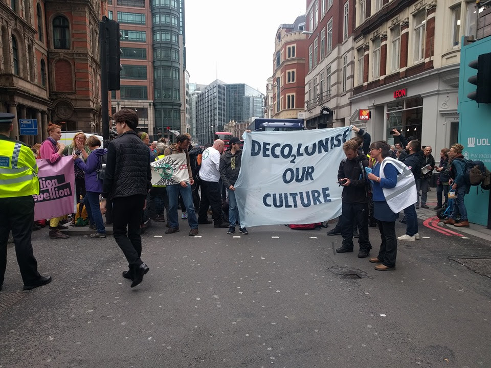 A roadblock on Bishopsgate in London, with around 30 rebels blocking the road. Some activists are holding a banner which reads 'DECO2LONISE OUR CULTURE'.