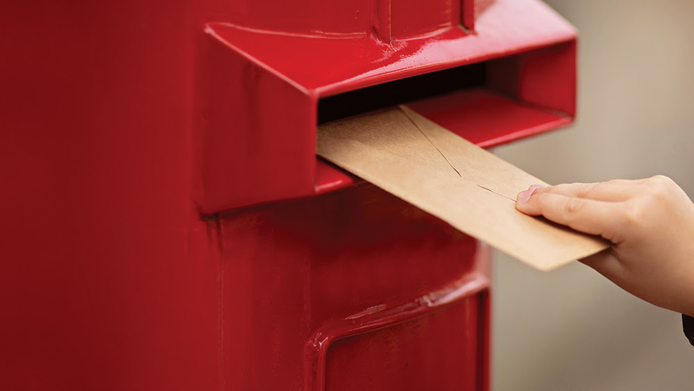 Letter bring put into a post box