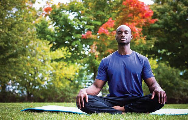 A man meditating outdoors.