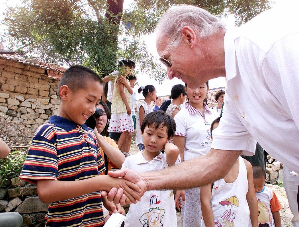 2001年,拜登访问燕子口村,与7岁的高山(音)握手。