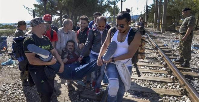 Un grupo de refugiados atraviesan la frontera entre Grecia y Macedonia, auxiliando a otro migrante. La mayoría proceden de Siria y atraviesan el autodenominado 'corredor de los Balcanes'. EFE/EPA/GEORGI LICOVSKI