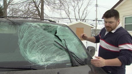 Adam Conley shows the damage done to his van.