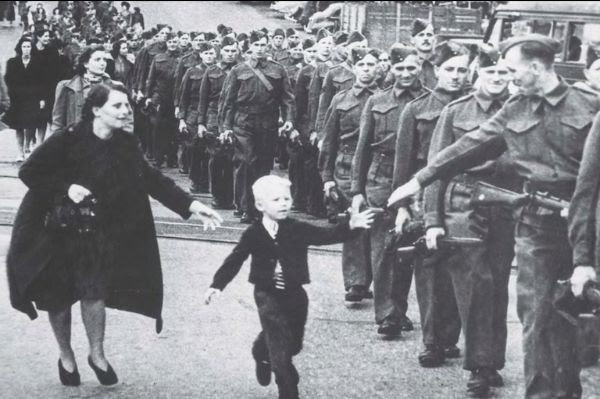 Boy reaches for his father's hand as he marches in a line of soldiers.