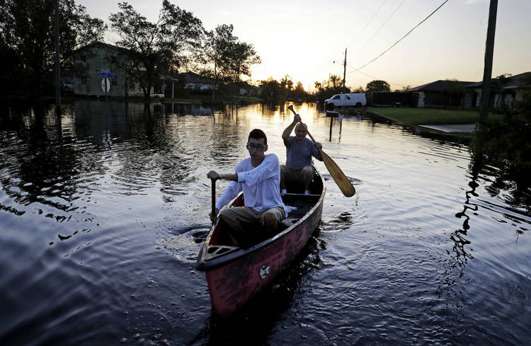 A father and son paddle though their flooded neighborhood in the aftermath of Hurricane Irma in Fort Myers, Fla. (AP/David Goldman)