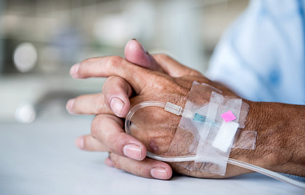 A closeup of hands with an attached IV.