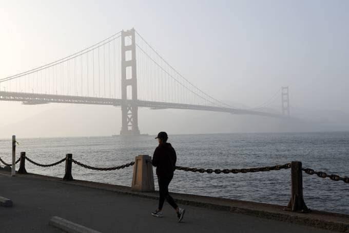 A person takes a walk along the waterfront near San Francisco's Golden Gate Bridge, shrouded in heavy haze due to the smoke. (John G. Mabanglo/EPA-EFE/Shutterstock)
