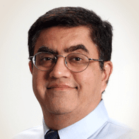 Dr. Chopra, a man with short black hair and glasses. He wears a white shirt and a tie