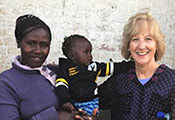 Dr. Debra Litzelman pictured with woman holding a baby at a research site in Kenya