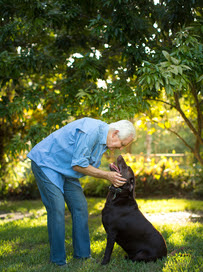 Older Caucasian Man Playing with Dog Outside
