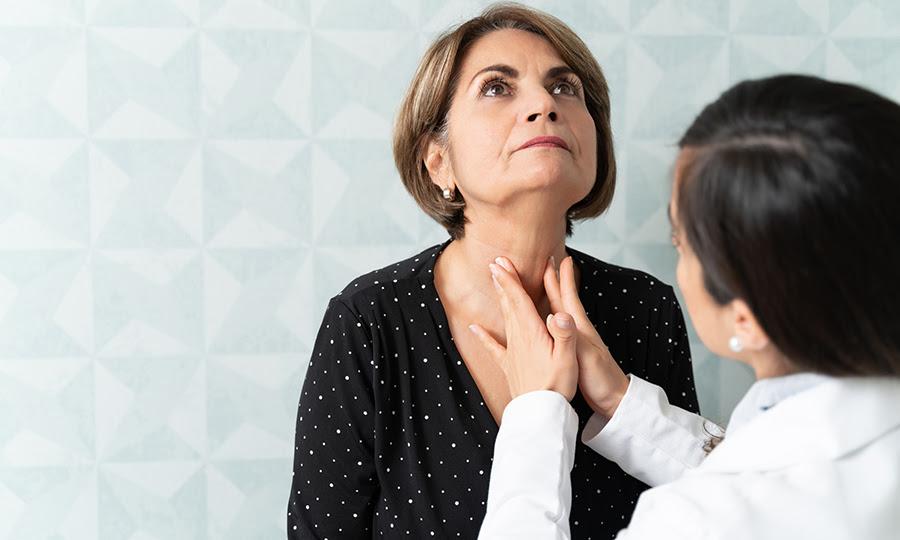Una foto de una paciente a la que un médico le revisa la tiroides
