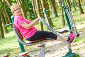 Woman using an outdoors gym - 10 things to do in a park this summer | Heart Matters - British Heart Foundation