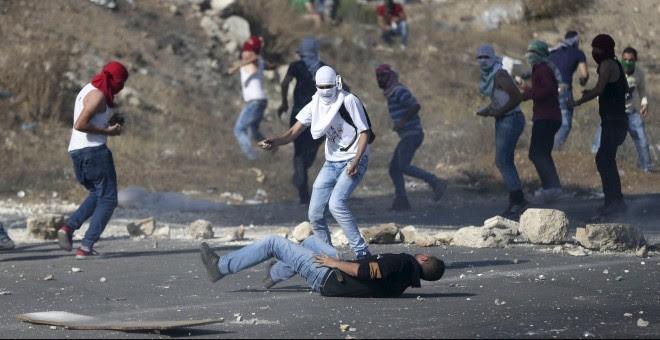 Un manifestante palestino herido yace en el suelo tras recibir un disparo de las tropas israelíes durante los enfrentamientos en el Hawara, puesto de control israelí cerca de la ciudad cisjordana de Naplusa.- REUTERS/Ahmad Talat