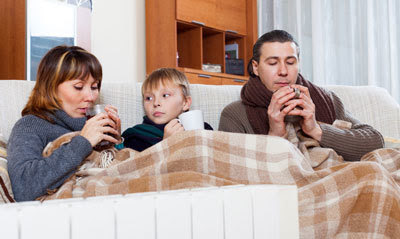 sick family bundled up on couch