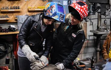 Jessi Combs watches over a women student during a welding lesson.