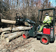 Man picking up logs with mini wheel loader grapple