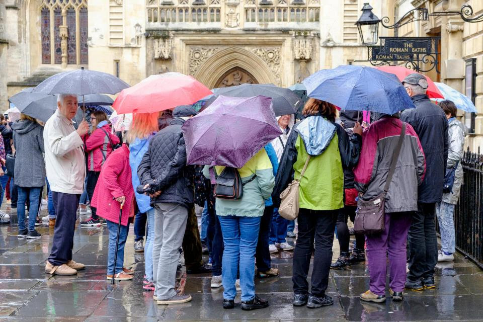While others in Bath huddled together as they stood in the pouring rain on a tour of the town on Wednesday