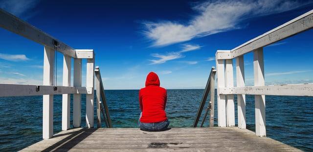 Persona vestida de rojo sentada al final de un muelle contemplando el horizonte en un día soleado.