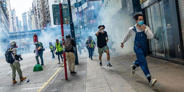 People in Hong Kong running away from tear gas fired by police during a protest against China's national security bill on May 24, 2020.