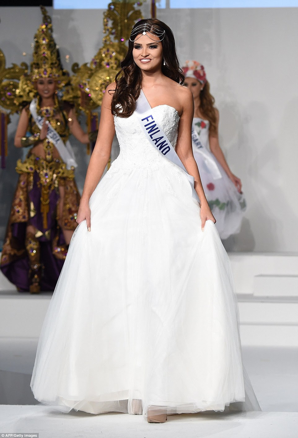 Miss FinlandSaara Ahlberg looked like she was expecting a groom to be at the end of the catwalk as she appeared in this wedding dress style gown and wearing a diamante tiara