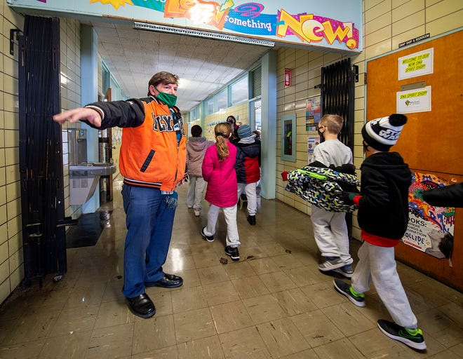 Principal Stephen DiCicco reminds students to social distance as they walk back to the classroom at St. Michael the Archangel School in Levittown on Friday.