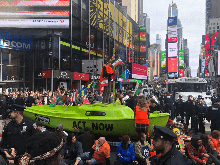 A bright, lime green boat in the middle of Times Square in New York, a very busy intersection of roads. The boat has the words 'ACT NOW' written in black on the side, with lots of police officers surrounding it. A young male activist is stood on top of the boat, which is adorned in the flags of nations which are at immediate risk from sea-level rise.