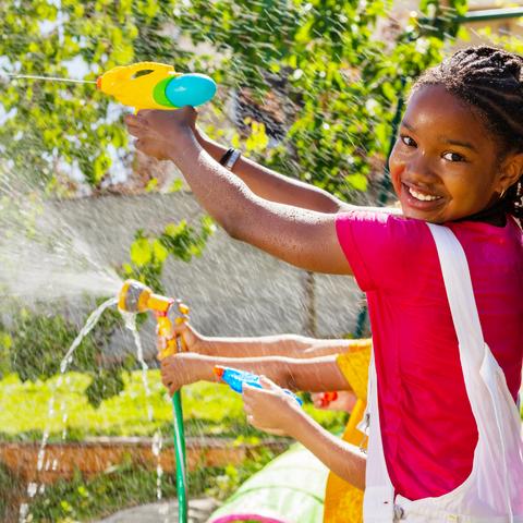 Petite fille jouant avec un pistolet à eau