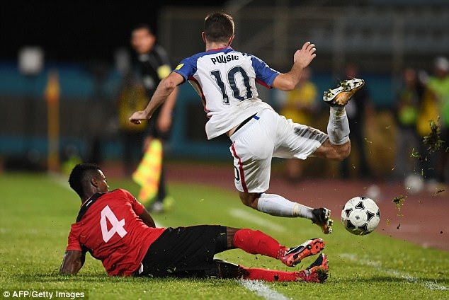 USA's Christian Pulisic (R) is marked by Trinidad and Tobago's Kevon Villaroel during their 2018 World Cup qualifier football match in Couva, Trinidad and Tobago