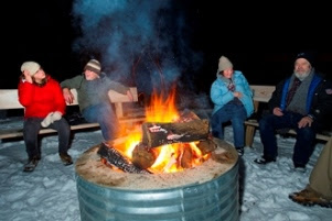 people sitting around a bonfire in winter