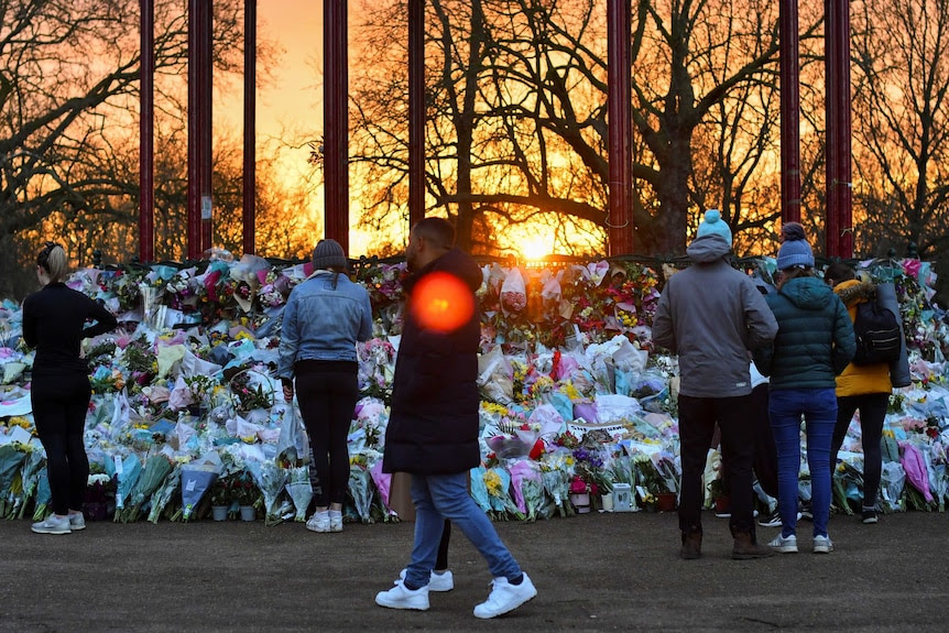 People walking past a huge pile of flowers as the sun sets