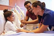 photo of a child in a hospital bed with a parent and physician
