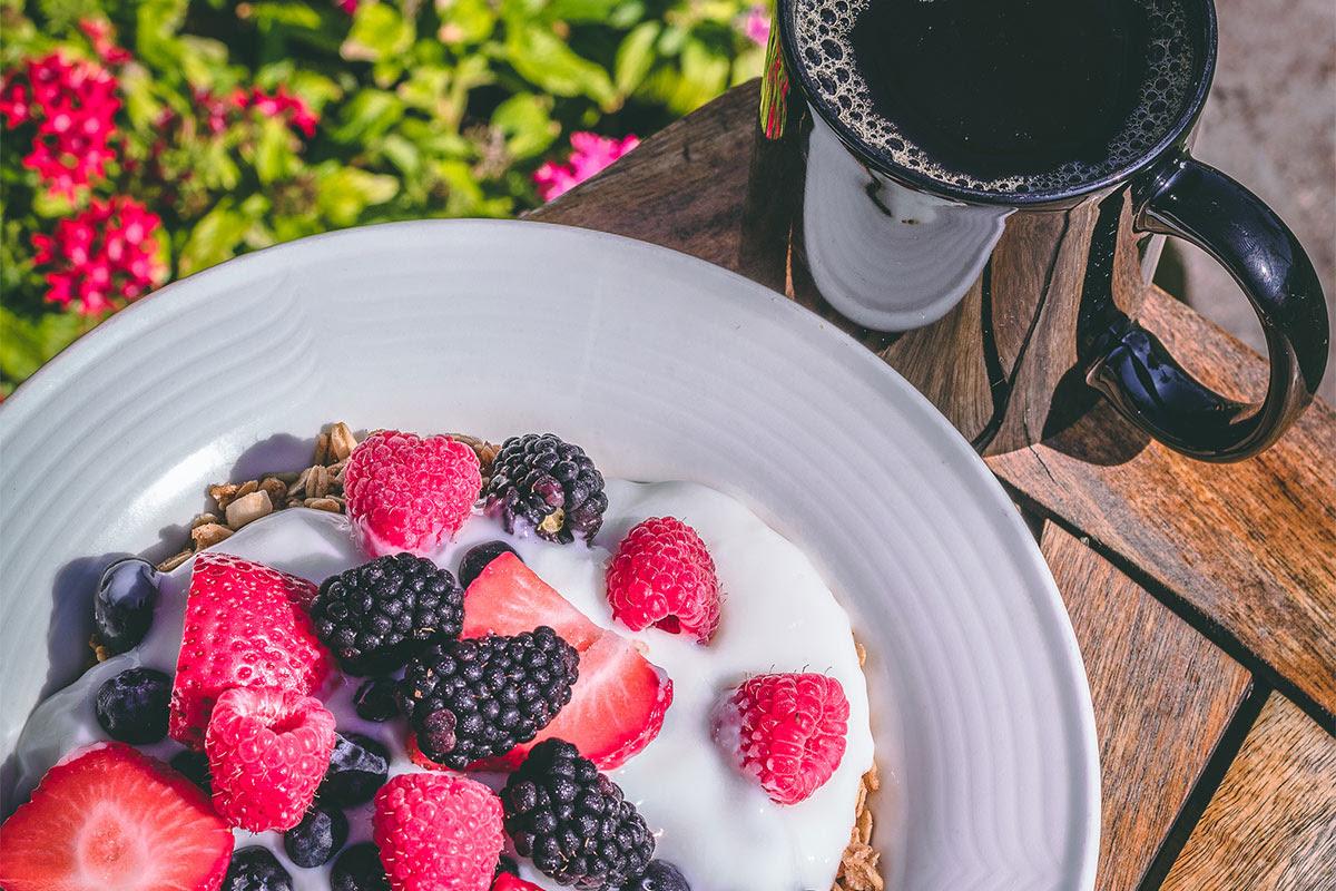 bowl of fruit and yogurt with mug of coffee