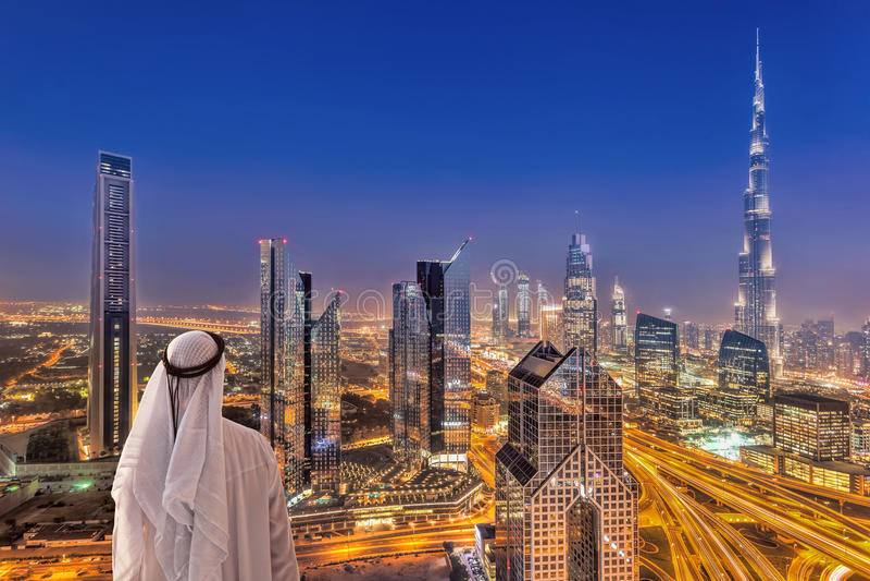 Arabian Man Watching Night Cityscape Of Dubai With Modern Futuristic  Architecture In United Arab Emirates Stock Photo - Image of east, hotel:  121393770