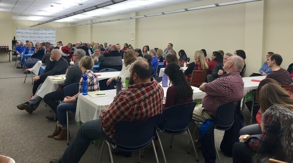 Wyoming Department of Education employees sit at tables filling a conference room during the all-staff meeting.