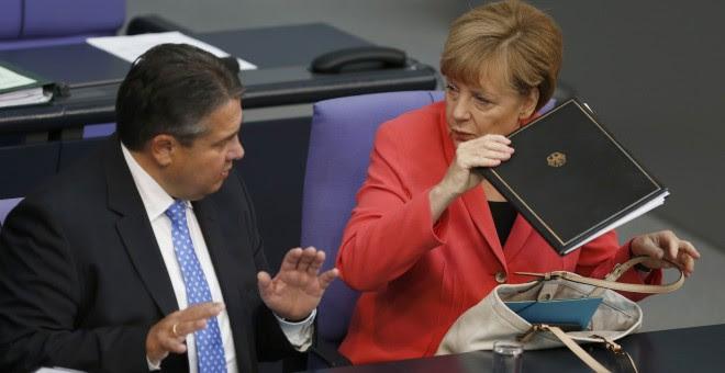 El vicecanciller  Sigmar Gabriel, con la canciller alemana Angela Merkel, en un debate del Bundestag sobre los refugiasdos. REUTERS/Hannibal Hanschke