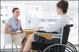 The figure above is a photograph showing two women talking in an office. One woman is in a wheelchair.