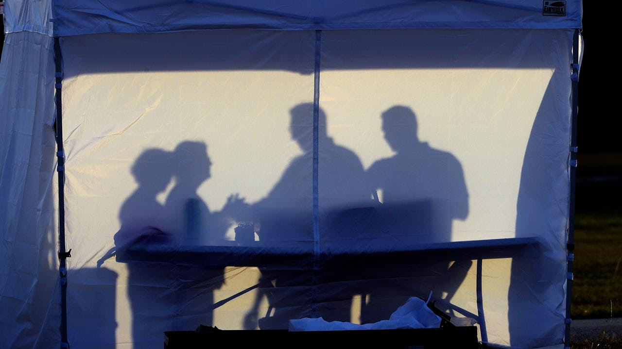 Medical personnel are silhouetted against the back of a tent before the start of coronavirus testing in a parking lot in Florida.