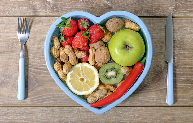Silverware and a heart-shaped bowl full of heart healthy foods.