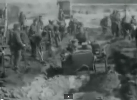 Region of Bergen-Belsen: SS has to                               dig out a mass grave and allies are                               helping with a bulldozer (6min. 48sec.)