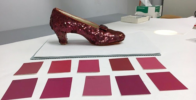 One of the Ruby Slippers seen with a range of ruby-colored paint chips as a quick color match