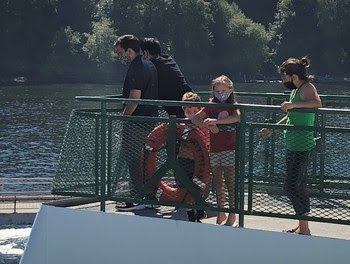 Photo of people wearing face coverings while on the outdoor deck of a ferry
