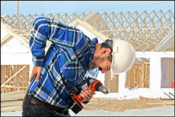 The figure above is a photograph showing a construction worker experiencing back pain.