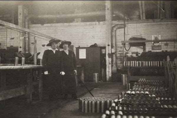 Black and white photo of two women in a munitions factory.