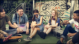 The figure shows a group of teenaged students sitting on the ground outdoors.